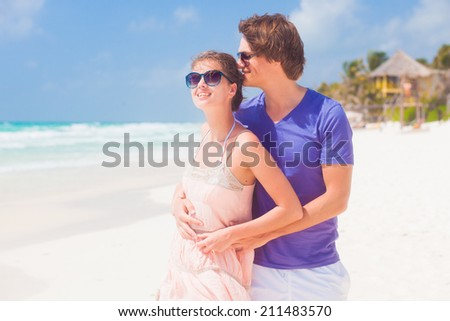 romantic couple hugging and holding hands at tropical beach - stock photo