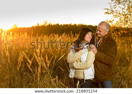 Romantic couple hugging during autumn sunset countryside looking at each other