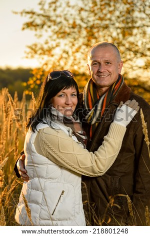 Romantic couple hugging in autumn countryside backlit by sunset