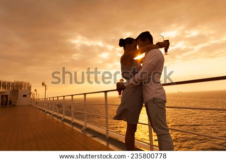 romantic couple hugging with eyes closed at sunset on a cruise ship - stock photo