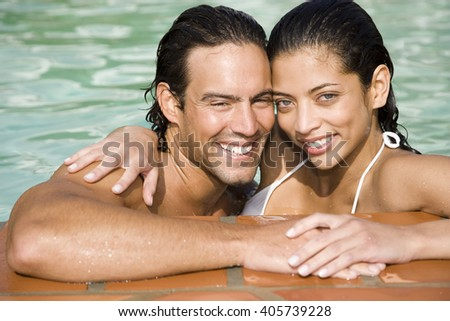 Romantic couple in a swimming pool on summer holiday