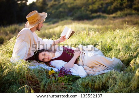 Romantic couple in historical clothing relax and read in a country setting
