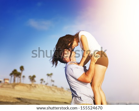 romantic couple in intimate moment on the beach. - stock photo