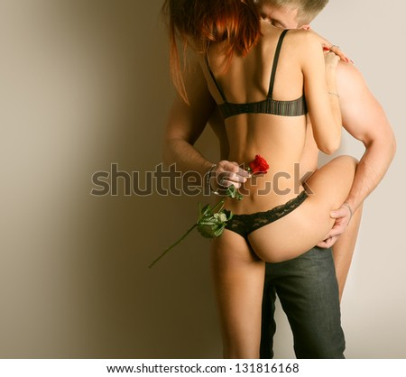 Romantic couple in lingerie with red rose on black background. - stock photo