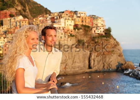 Romantic couple in love by sunset on holidays travel. Young beautiful couple enjoying ocean view romance. Young people, man and woman traveling on vacation in Manarola, Cinque Terre, Liguria, Italy - stock photo