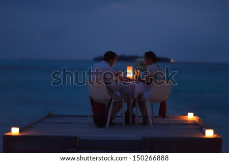 romantic couple  in love have dinner in outdoor restaurant with candles with sea in background - stock photo