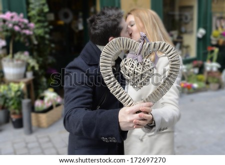 Romantic couple in love holding a heart and kissing on Valentines day - stock photo