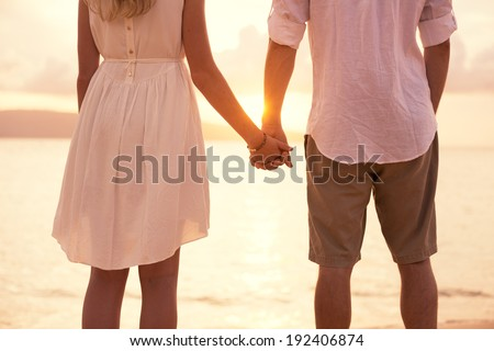 Romantic couple in love holding hands on the beach sunset - stock photo