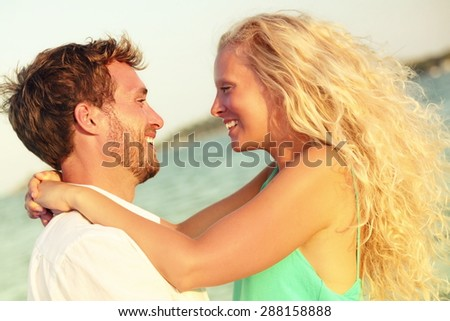 Romantic couple in love kissing happy at beach sunset. Young happy man and woman on in romance on summer beach during honeymoon vacation holidays travel. - stock photo