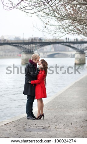 Romantic couple in love kissing near Pont des Arts in Paris - stock photo