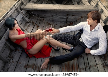 Romantic couple in love with wineglasses of red wine in old boat on sunset - stock photo