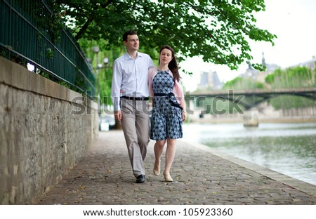 Romantic couple is having a stroll by the Seine in Paris - stock photo