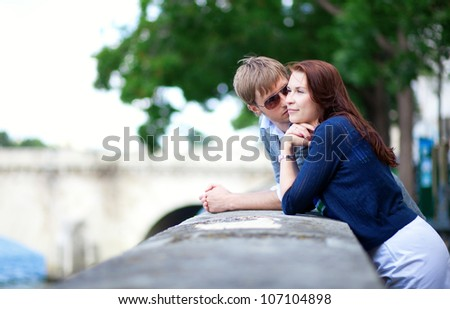 Romantic couple is talking at the Seine embankment in Paris - stock photo