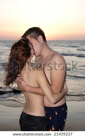 Romantic couple kissing at seaside on sunset