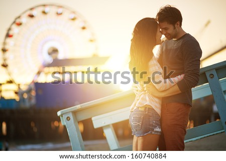 romantic couple kissing at sunset in fromt of santa monica ferris wheel. - stock photo