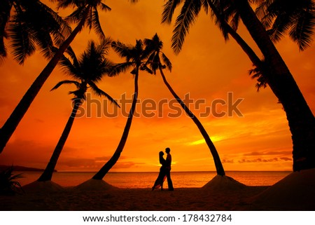 Romantic couple kissing at tropical beach with palm trees with sunset in the background - stock photo