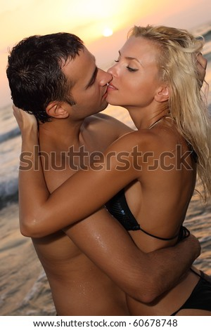 Romantic couple kissing on a beach at sunset - stock photo