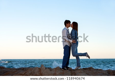 Romantic couple kissing on rocks at seaside. - stock photo