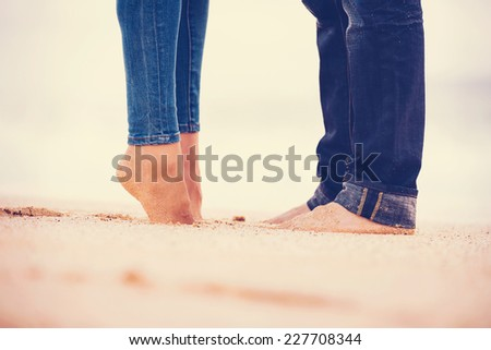 Romantic Couple Kissing on the Beach at Sunset - stock photo