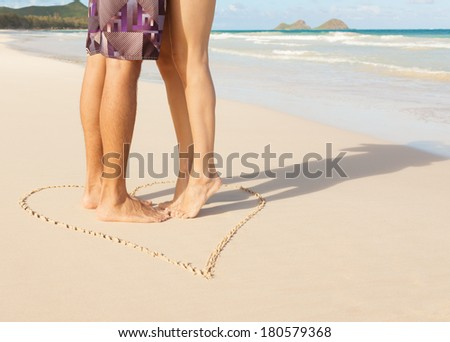 Romantic couple kissing on the beach. Love - male and female feet in the heart on the beach.  - stock photo