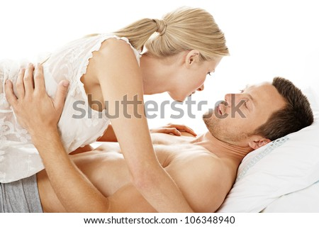 Romantic couple kissing while in bed. - stock photo