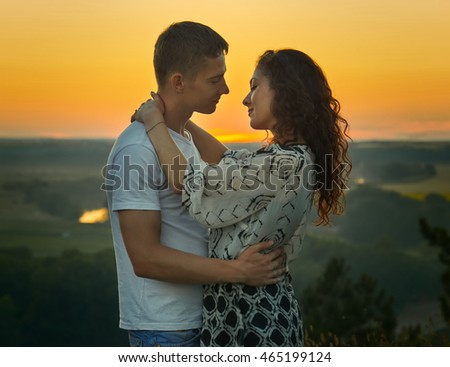 romantic couple looking at each other at sunset on outdoor, beautiful landscape and bright yellow sky, love tenderness concept, young adult people