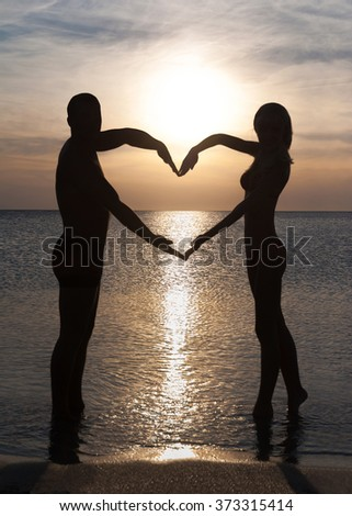 Romantic couple making heart shape by hands at beach against sea surface and sunset brilliance at water ripples, Saint Valentines Day greeting card concept, Vertical background