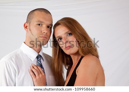 Romantic couple, man and woman, standing in an embrace and looking at the camera - stock photo