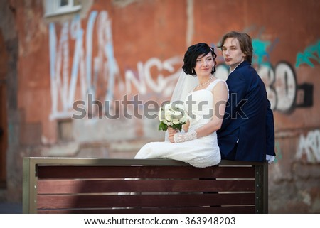 Romantic couple of bride and groom sitting and posing in old town street