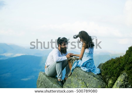 Romantic couple of pretty woman or girl and handsome bearded man with beard on cliff on summer day over mountain tops with blanket