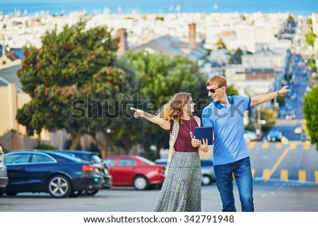 Romantic couple of tourists using tablet and planning their itinerary in San Francisco, California, USA