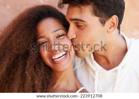 Romantic Couple On Holiday Together Posing By Wall