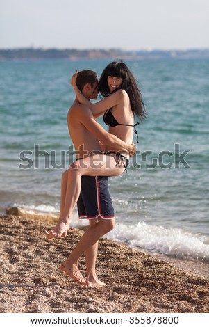 Romantic couple on seashore. Young man carries laughing girl in sea