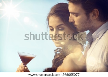 Romantic couple on summer holiday enjoying sunset with a drink.