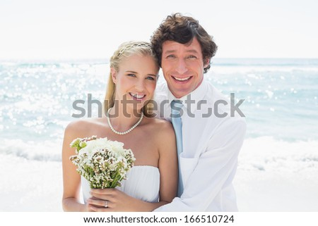 Romantic couple on their wedding day smiling at camera at the beach