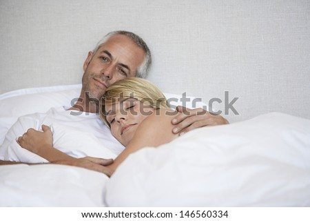 Romantic couple relaxing in bed at home - stock photo
