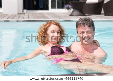 Romantic couple relaxing in the pool at summer