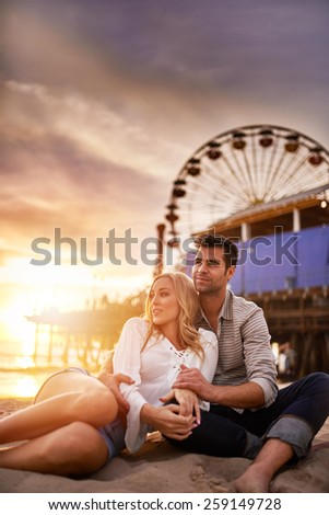 romantic couple relaxing on beach at santa monica with copy space - stock photo