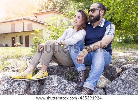 romantic couple relaxing on the banks of a river in summer