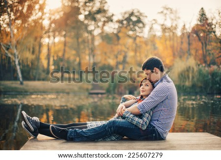 Romantic couple relaxing on the river dock in autumn park