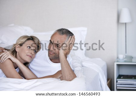 Romantic couple relaxing together on bed in bedroom
