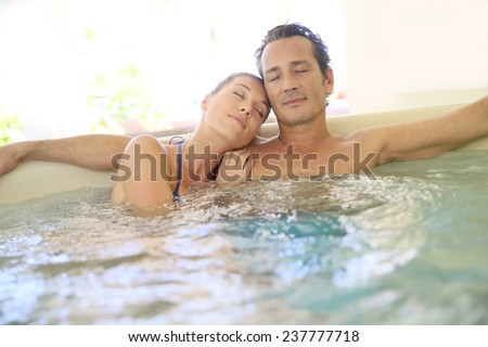 Romantic couple relaxing with eyes shut in jacuzzi - stock photo