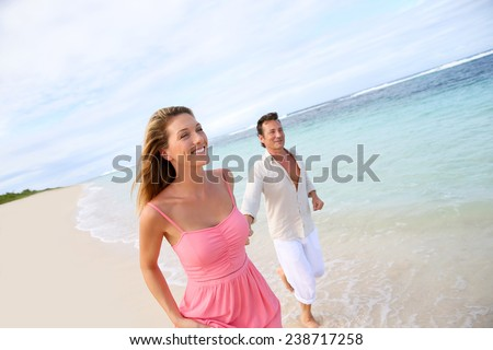 Romantic couple running on a sandy beach - stock photo