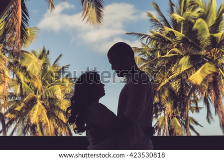 Romantic Couple / Silhouette of couple under coconut trees by the beach layered - stock photo