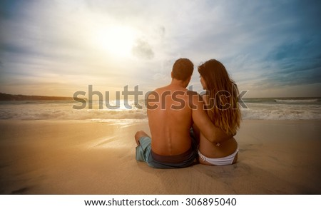 Romantic couple siting on beach and looking sunset - stock photo