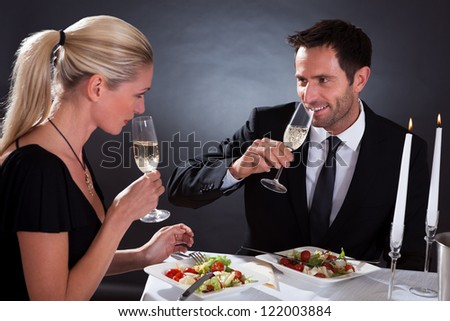 Romantic couple sitting having dinner in an elegant restaurant toasting each other with flutes of champagne - stock photo
