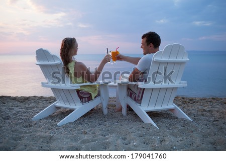 Romantic couple sitting in wooden deckchairs on the beach toasting the sunset clinking their cocktail glasses together, view from behind looking out to sea