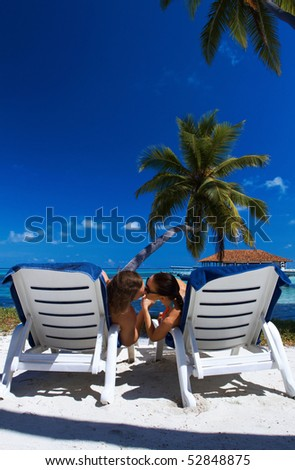 Romantic couple sitting next to palm tree
