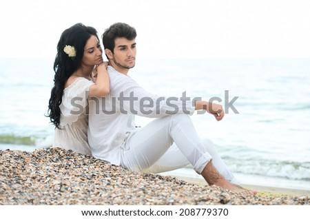Romantic couple sitting on a beach  - stock photo