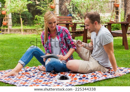 Romantic couple sitting on a blanket with tablet pc and mobile phone at summer green park. They are happy. - stock photo